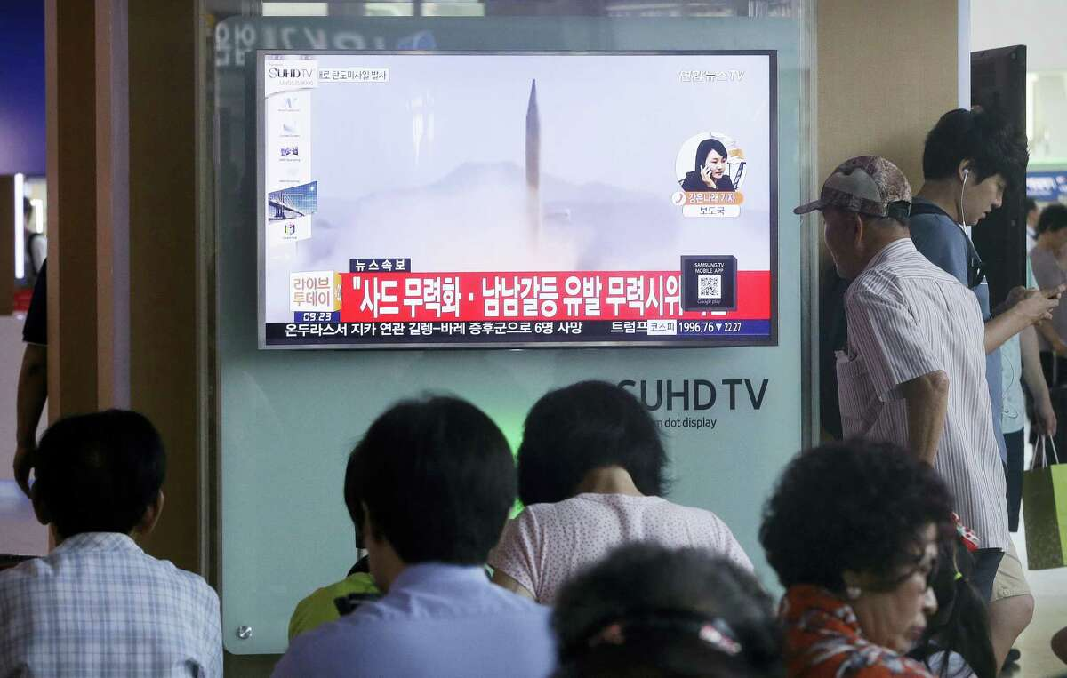 """South Koreans watch a TV news program airing file footage of a North Korean rocket launch at the Seoul Railway Station in Seoul, South Korea on Aug. 3, 2016. North Korea fired a ballistic missile into the sea on Wednesday, South Korea's military said, the fourth reported weapons launch the North has carried out in about two weeks. The characters read """"Against a deployment of the Terminal High-Altitude Area Defense."""""""