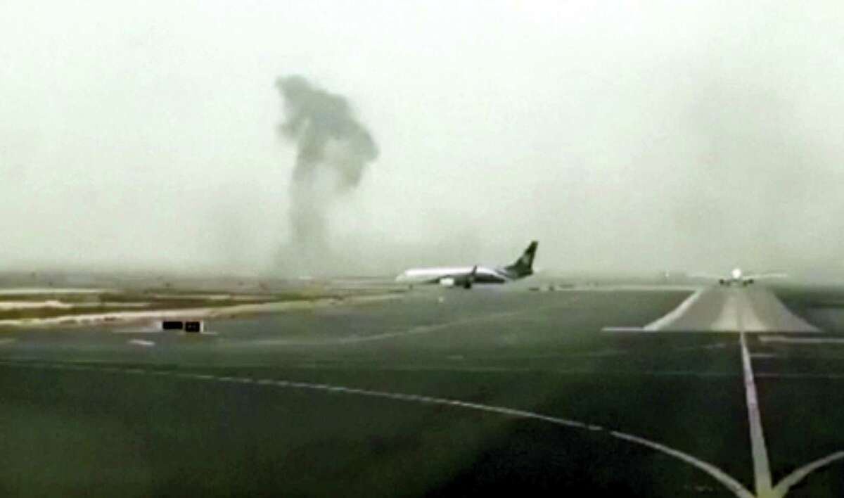 This image made from video shows smoke rising after an Emirates flight crash landed at Dubai International Airport on Aug. 3, 2016. The plane at right was unaffected. Dubai-based airline Emirates has confirmed that there were no fatalities on a flight from India that crash-landed.
