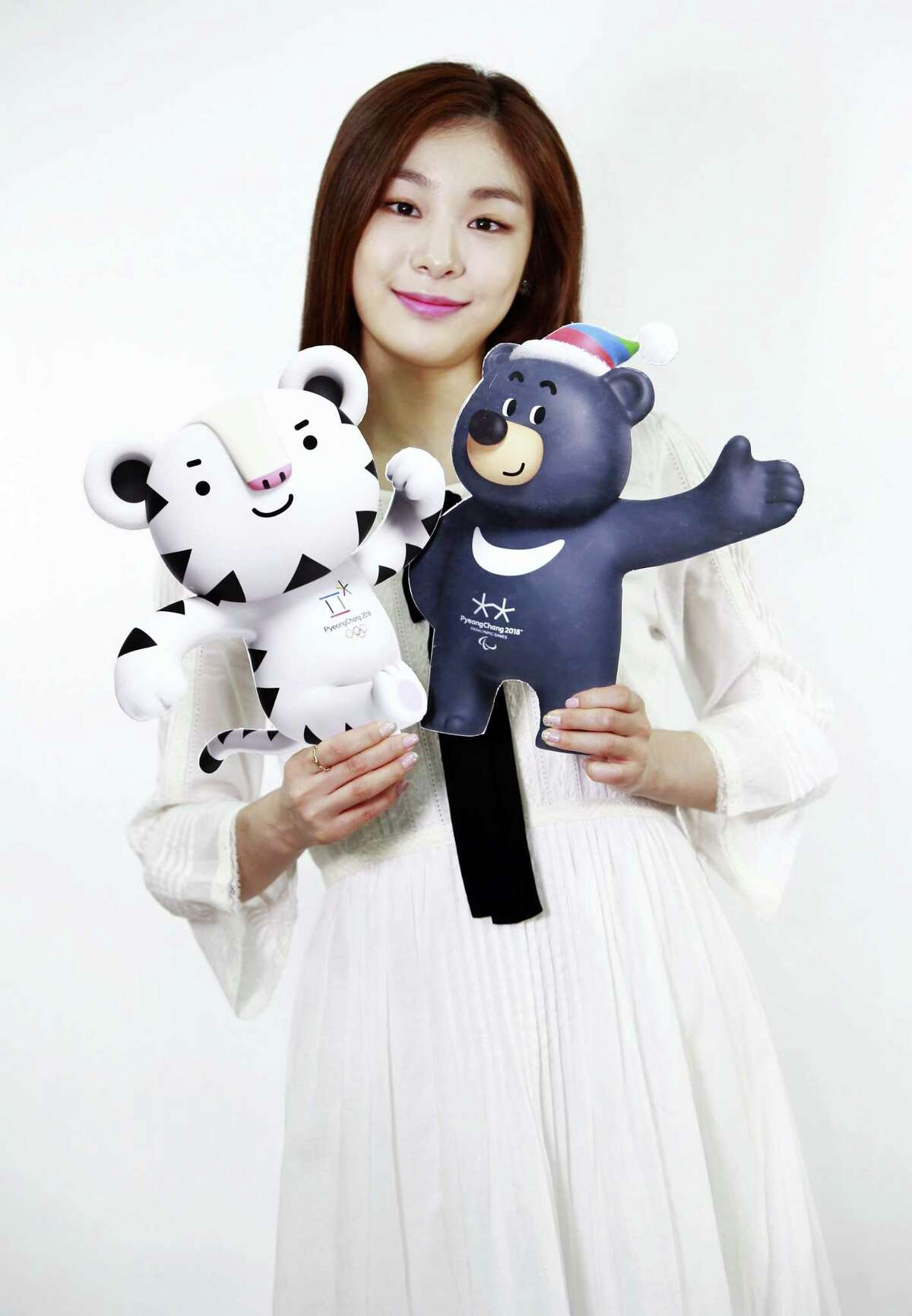 In this photo provided by the PyeongChang Organizing Committee for the 2018 Olympic & Paralympic Winter Games, a former South Korean Olympic figure skater Yuna Kim who is an honorary ambassador for the 2018 Winter Olympics, holds the cut-outs of the official mascots for the 2018 PyeongChang Olympics, named Soohorang, left, and Paralympic Winter Games, named Bandabi, right, in Seoul, South Korea on Thursday.