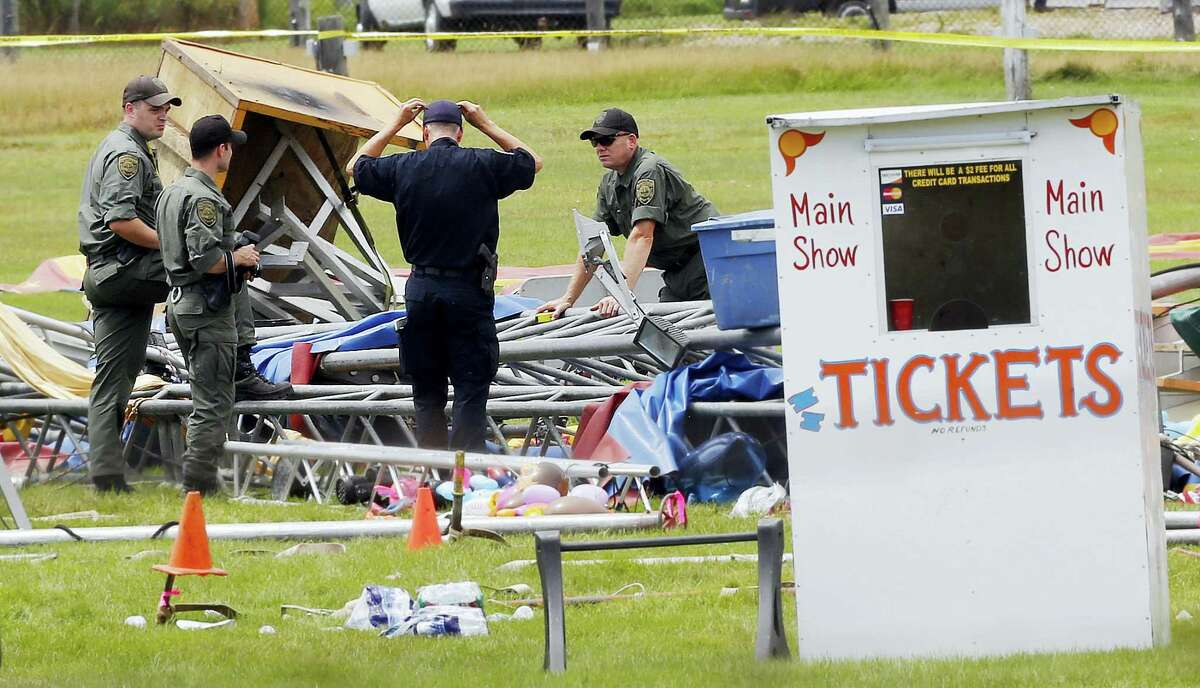 In a Aug. 4, 2015, file photo, investigators work at the scene of a circus tent that collapsed, killing a father and his 6-year-old daughter in Lancaster, N.H. A year after the circus tent collapsed, a Florida-based circus operator faces numerous charges and lawsuits. About 100 people were inside the tent on Aug. 3, 2015, at the Lancaster Fairgrounds when a storm blew through, toppling it.