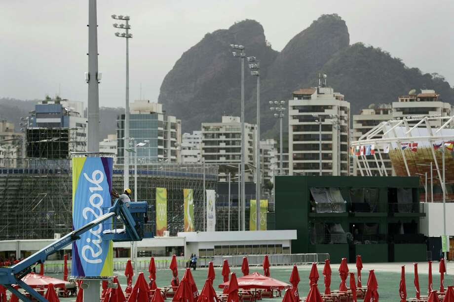 A worker hangs a banner at the Olympic Park ahead of the 2016 Summer Olympics in Rio de Janeiro, Brazil on Wednesday. Photo: ASSOCIATED PRESS  / Copyright 2016 The Associated Press. All rights reserved. This material may not be published, broadcast, rewritten or redistribu