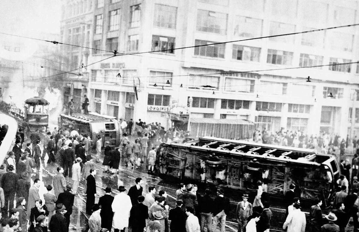 """FILE - In this April 9, 1948, file photo, a streetcar lays overturned outside the Granada Hotel in Bogota, Colombia during an uprising after the death of Jorge Eliecer Gaitan. The mob also sacked and set fire to the government house, right. The 1948 assassination of populist firebrand led to a political bloodletting known as """"The Violence."""" Tens of thousands died, and peasant groups joined with communists to arm themselves. A 1964 military attack on their main encampment led to the creation of the Revolutionary Armed Forces of Colombia, or FARC."""