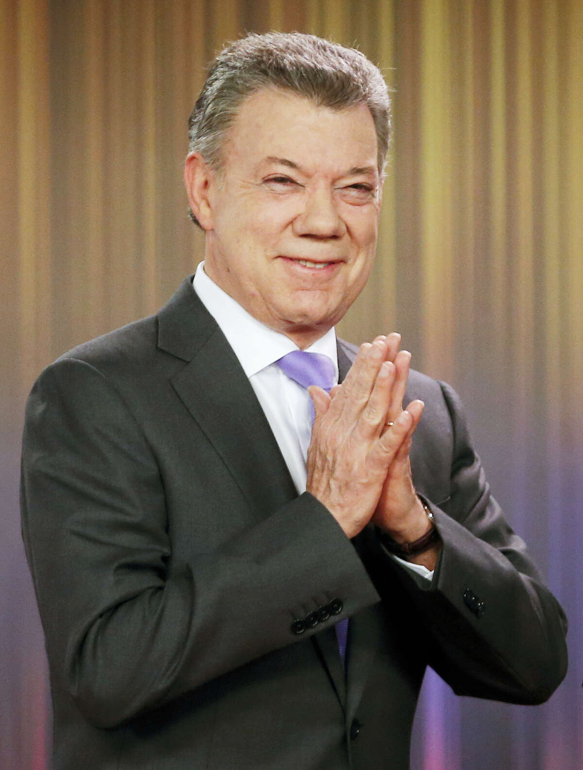 Colombia's President Juan Manuel Santos holds his hands as he arrives to deliver a statement at the presidential palace in Bogota, Colombia, Friday, Oct. 7, 2016. Santos won the Nobel Peace Prize Friday, just days after voters narrowly rejected a peace deal he signed with rebels of the Revolutionary Armed Forces of Colombia, FARC.