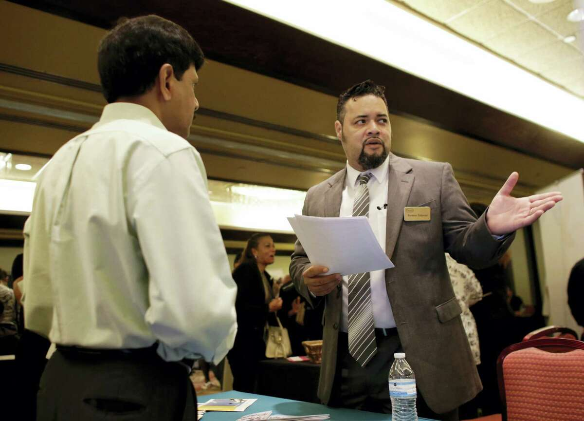 In this July 19, 2016 photo, Ronnie Teheran, with Service Corporation International, right, talks with a job applicant at a job fair in Miami Lakes, Fla.