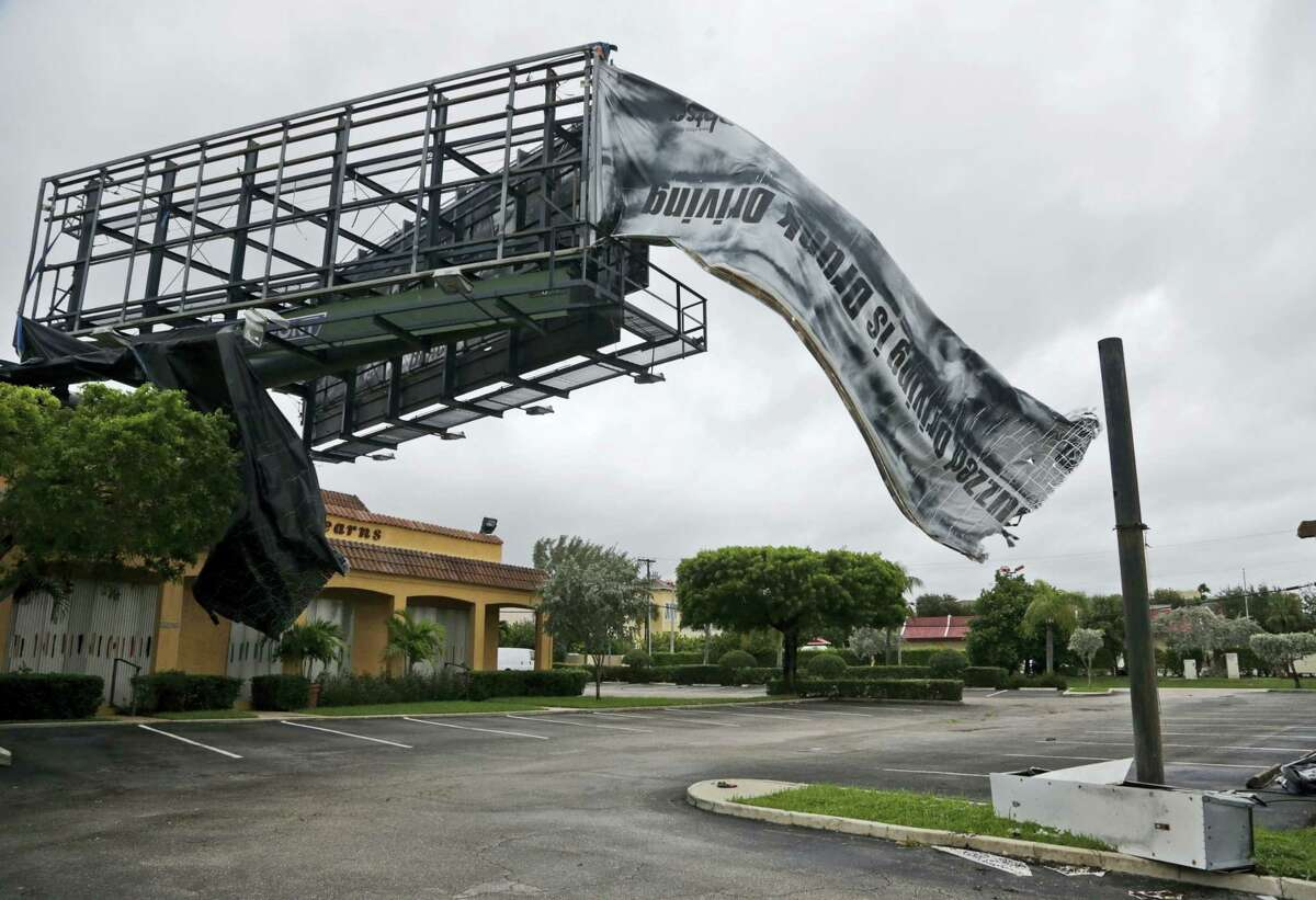 A billboard canvas flaps in the wind after Hurricane Matthew passed off shore, Friday, Oct. 7, 2016, in North Palm Beach, Fla. Matthew was downgraded to a Category 3 hurricane overnight with the strongest winds of 120 mph just offshore as the storm pushed north, threatening hundreds of miles of coastline in Florida, Georgia and South Carolina.