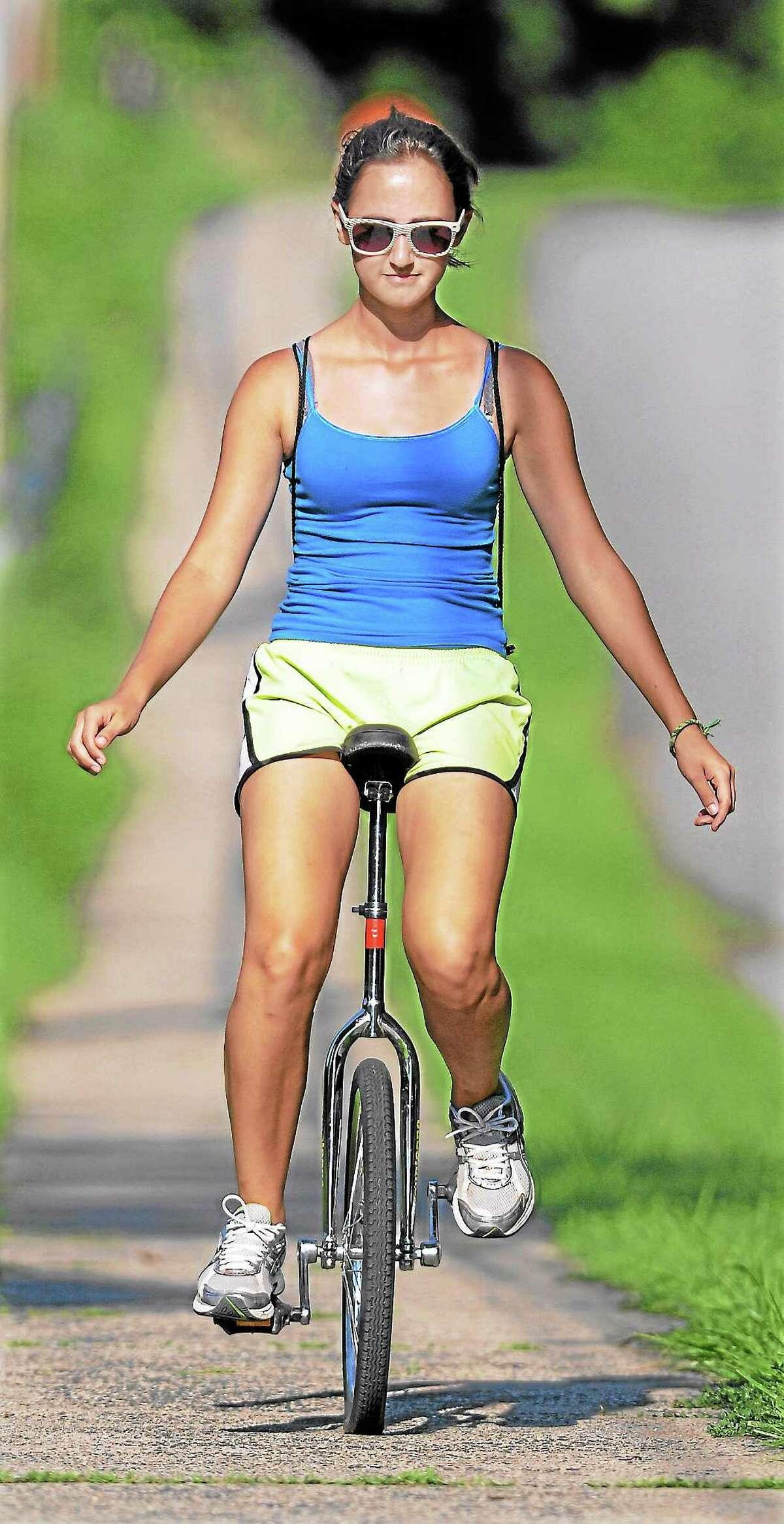 Eva Varszegi rides her unicycle down Wadsworth Street in Middletown.