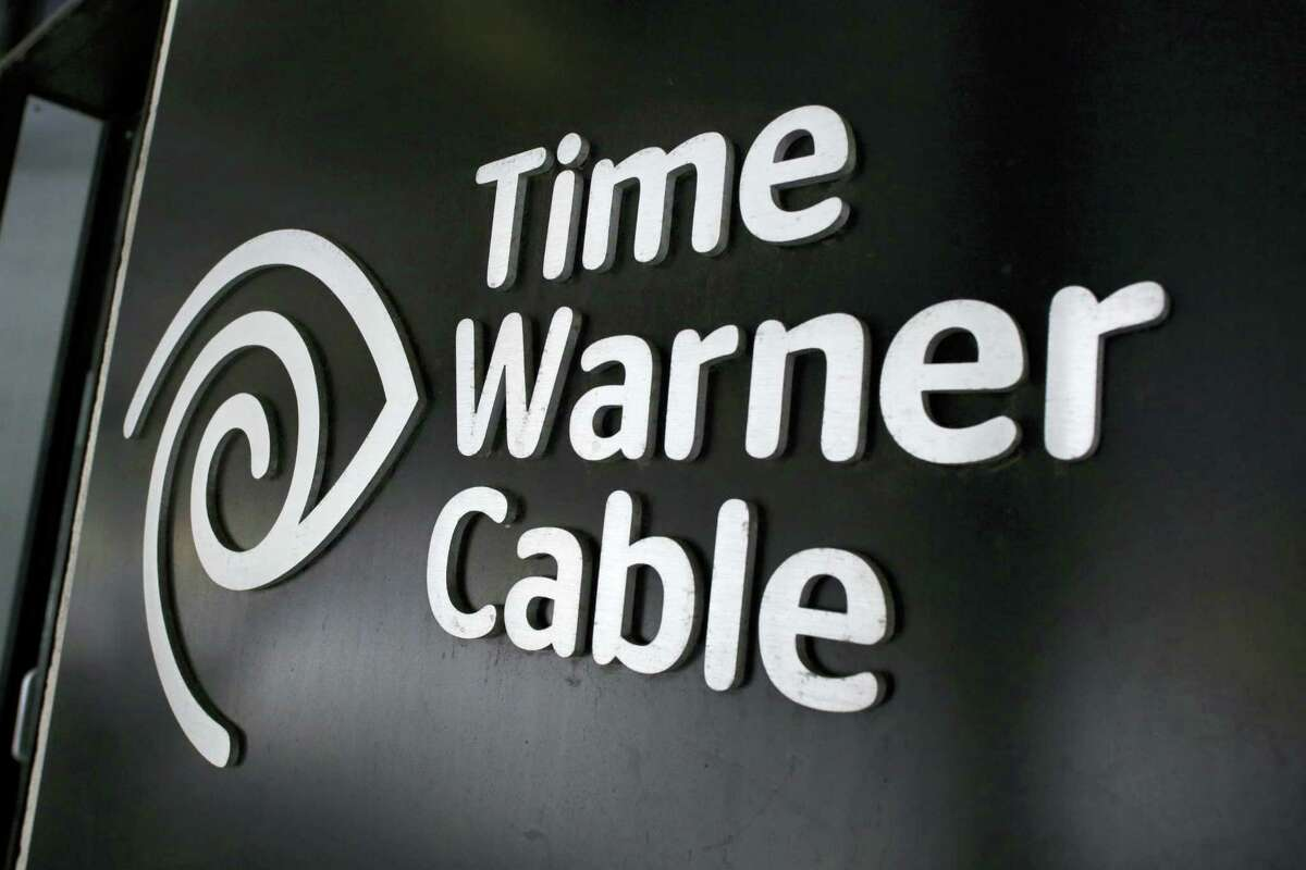 In this file photo, the Time Warner Cable corporate logo is displayed at a company store, in New York.
