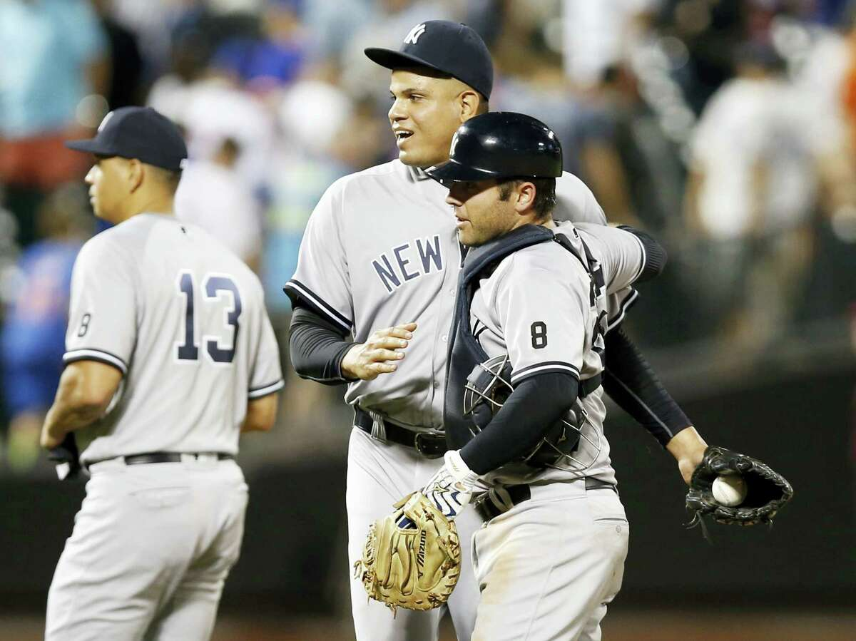 New York Yankees relief pitcher Dellin Betances, center, celebrates with Yankees catcher Austin Romine after the Yankees defeated the Mets 6-5 in the tenth inning of an interleague game Monday in New York. New York Yankees Alex Rodriguez (13), who did not play, leaves the field after celebrating with teammates.