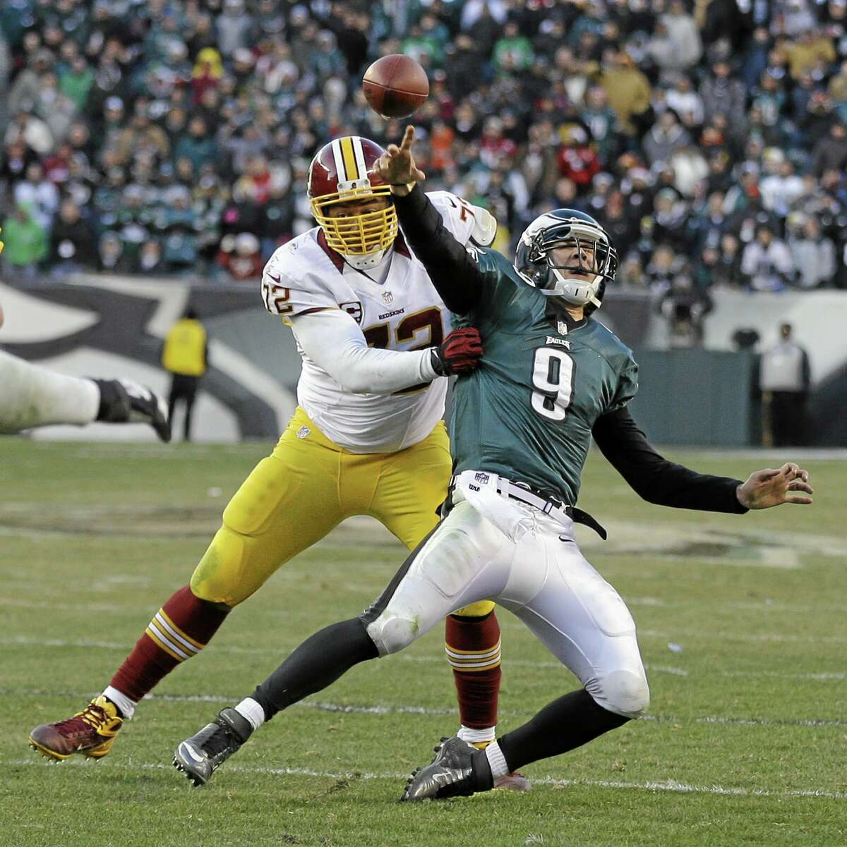Philadelphia Eagles' Nick Foles passes the ball as Washington Redskins' Stephen Bowen brings him down during the final seconds of an NFL football game on Dec. 23, 2012, in Philadelphia. Foles was called for intentional grounding on the game-ending play. Washington won 27-20.