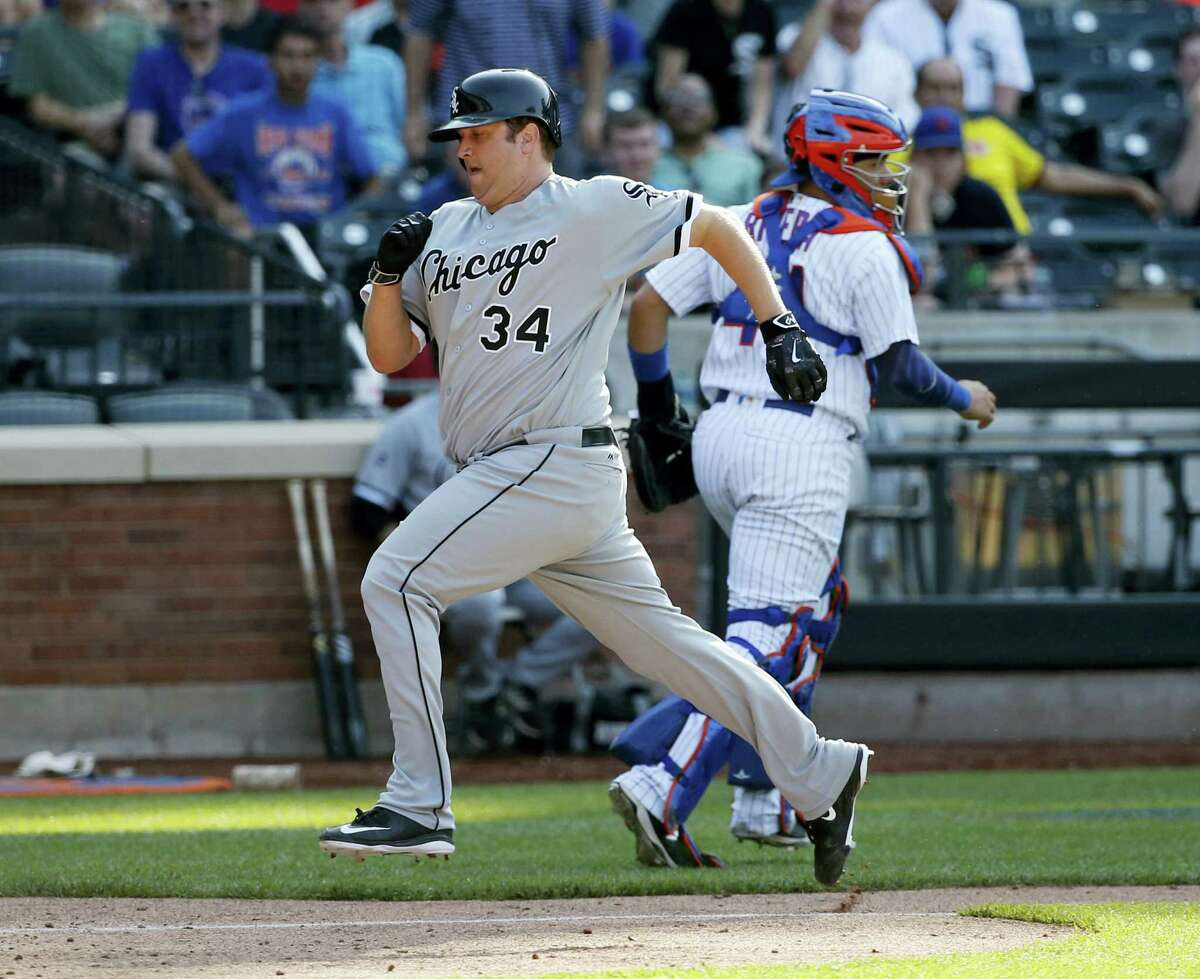 Chicago White Sox Matt Albers (34) scores on Jose Abreu's 13th-inning sacrifice fly against the New York Mets, Wednesday. New York Mets catcher Rene Rivera (44) chases down the off-line throw.