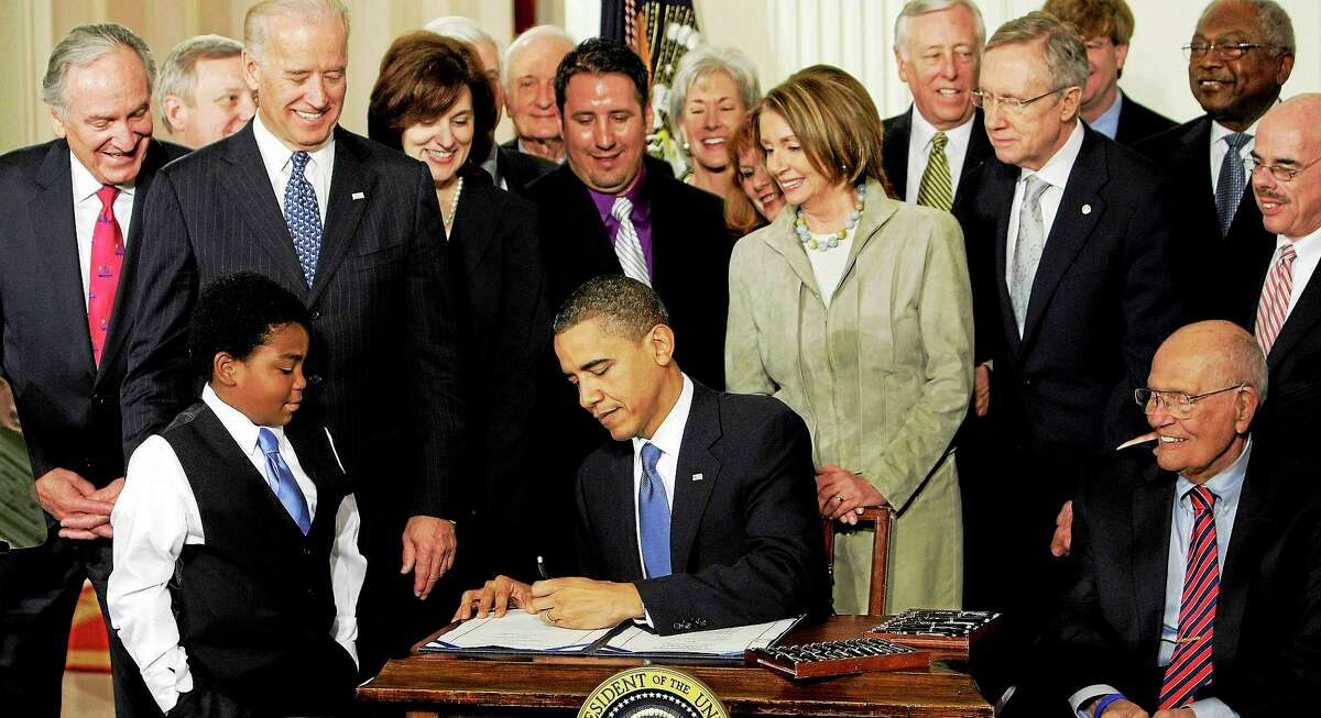 In this March 23, 2010, photo, President Barack Obama signs the Affordable Care Act in the East Room of the White House in Washington.