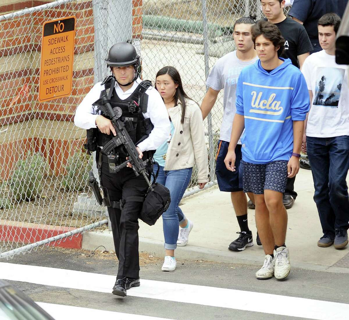 Law enforcement evacuate students away from the scene of a fatal shooting at the University of California, Los Angeles, Wednesday, June 1, 2016, in Los Angeles.