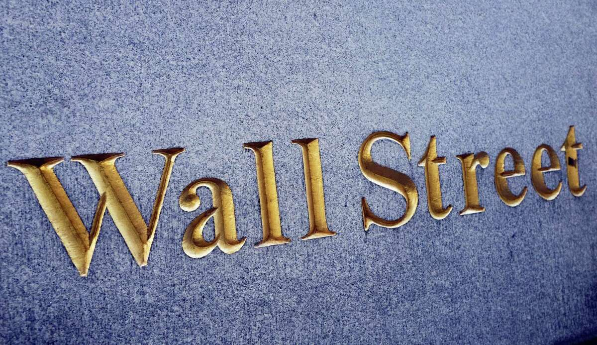 A sign for Wall Street is carved into a building located near the New York Stock Exchange, Friday, Oct. 7, 2016. Solid, if uninspiring, U.S. jobs data had little impact on financial markets Friday on a day when much of the focus was on the British pound, which briefly and mysteriously plummeted to a new 31-year low against the dollar.