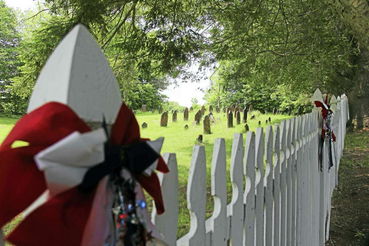 Katherine Schassler — The Middletown Press The historic Old North Burying Ground in Middlefield is decked out in patriotic bunting.
