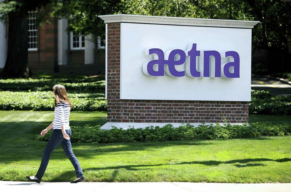 In this Aug. 19, 2014 photo, a pedestrian walks past a sign for health insurer Aetna Inc., at the company headquarters in Hartford, Conn.