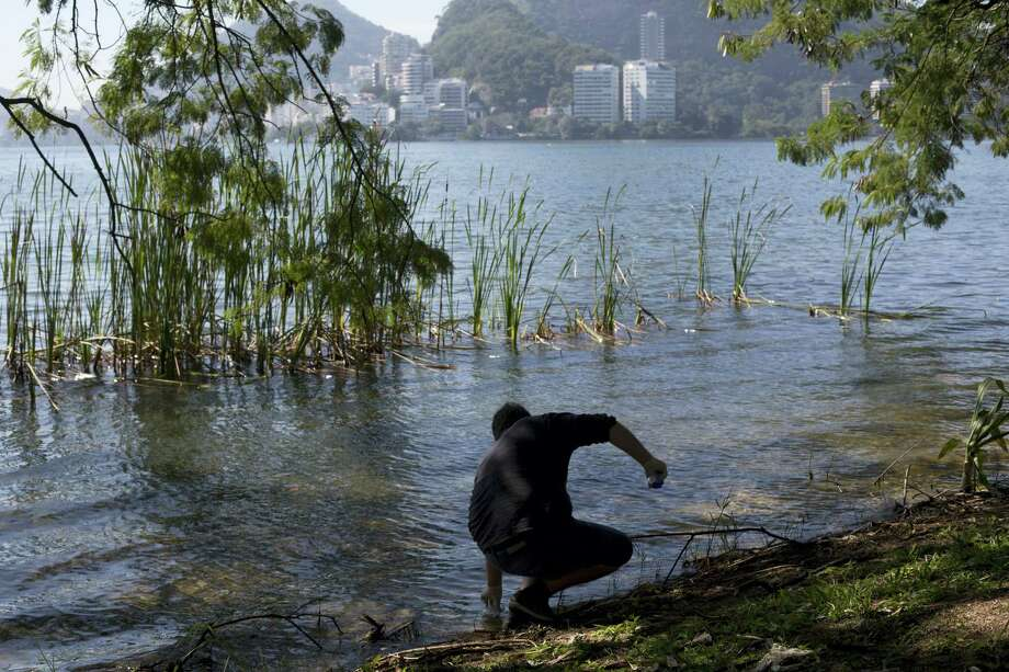 In this July 11, 2016 photo, doctoral candidate Rodrigo Staggemeier collects water from Rodrigo de Freitas Lake for a water quality study commissioned by The Associated Press in Rio de Janeiro, Brazil. At the conclusion of the 16-month study that has revealed consistent and dangerously high levels of illness-causing viruses from the human sewage pollution in aquatic Olympic venues, the local Olympic organizing committee did not respond to multiple requests for comment. They have previously said Rio state's own bacterial testing has shown the aquatic venues to be within state guidelines. Photo: AP Photo/Silvia Izquierdo  / Copyright 2016 The Associated Press. All rights reserved. This material may not be published, broadcast, rewritten or redistribu