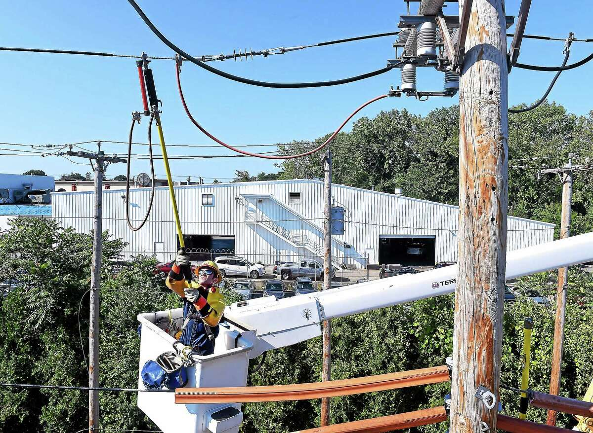 A United Illuminating lineworker apprentice replaces an underarm disconnect in this 2014 photo. This procedure separates and isolates circuits to facilitate the restoration of power during power outages.