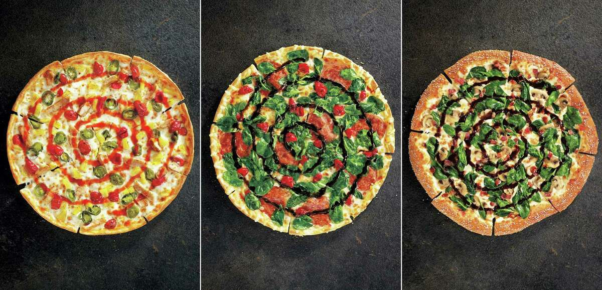 This product image provided by Pizza Hut shows the restaurant chain's specialty pizzas: from left, Sweet Sriracha Dynamite, Cherry Pepper Bombshell, and Pretzel Piggy.