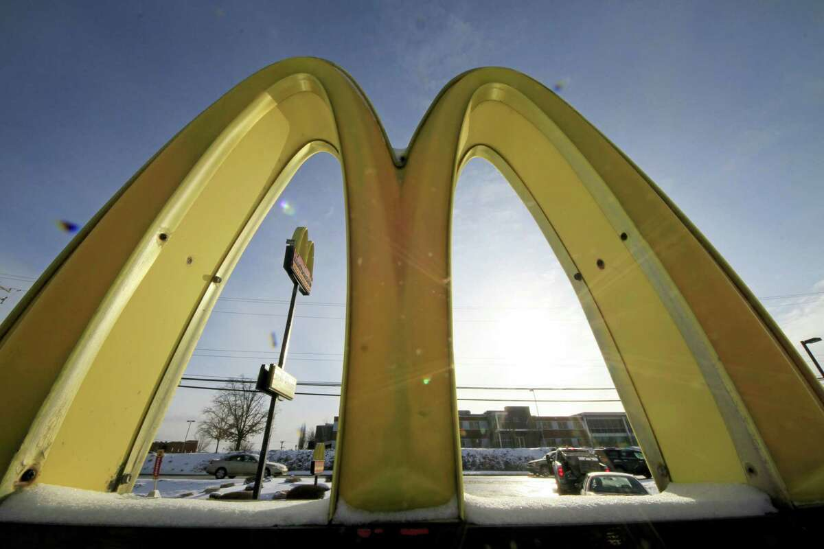 In this Jan. 21, 2014 photo, cars drive past the McDonald's Golden Arches logo at a McDonald's restaurant in Robinson Township, Pa.