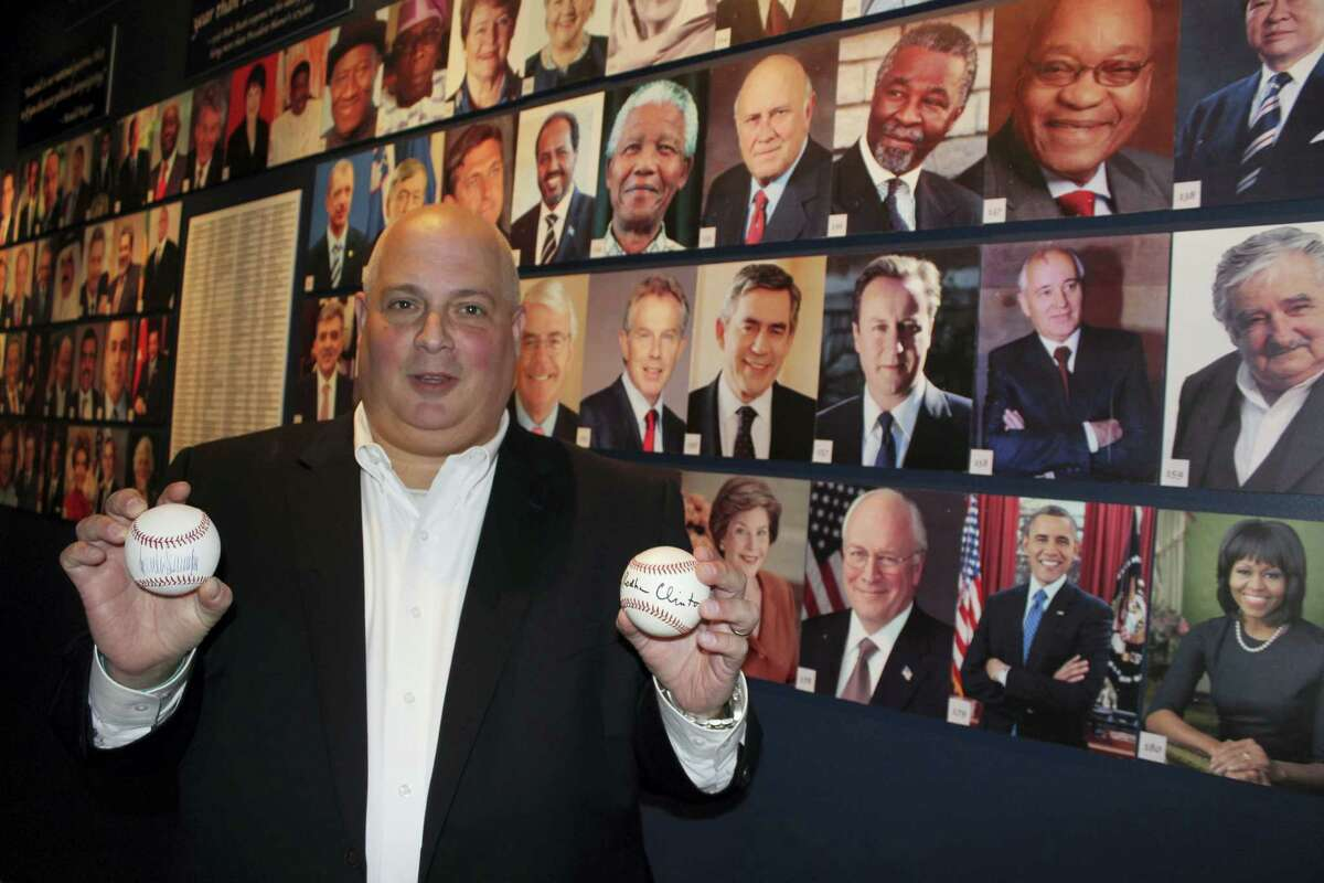 In this photo taken Sept. 30, 2016, Randy Kaplan holds autographed baseballs in Garden City, N.Y., signed by presidential candidates Donald Trump and Hillary Clinton. Kaplan has collected more than 200 signed baseballs from world leaders, including current and former U.S. presidents, prime ministers and others. The baseballs are on display at the Cradle of Aviation Museum on Long Island through next month's election.