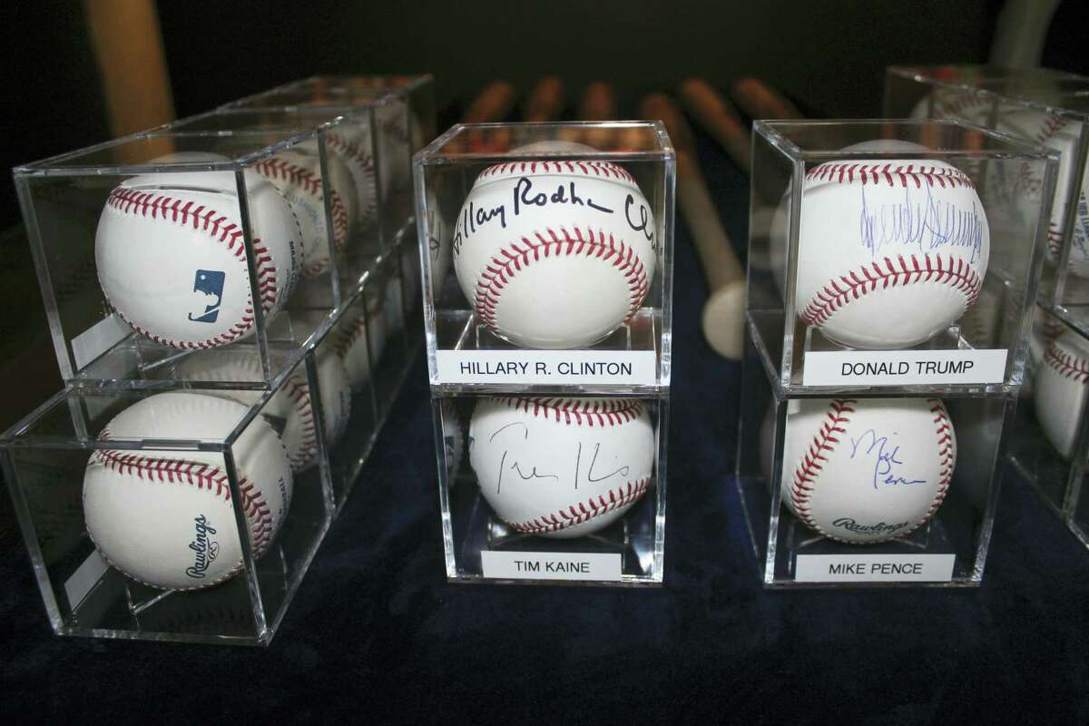In this photo taken Sept. 30, 2016, autographed baseballs signed by Democratic and Republican presidential candidates Hillary Clinton and Donald Trump, and their running mates Tim Kaine and Mike Spence, are on display in Garden City, N.Y., at the Cradle of Aviation Museum.