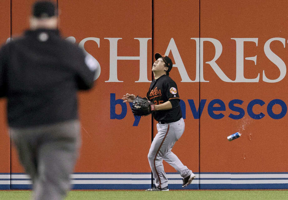 Baltimore Orioles' Hyun Soo Kim gets under a fly ball as a can falls past him during the seventh inning of an American League wild-card baseball game against the Toronto Blue Jays in Toronto on Oct. 4, 2016. Photo: Mark Blinch/The Canadian Press Via AP  / The Canadian Press