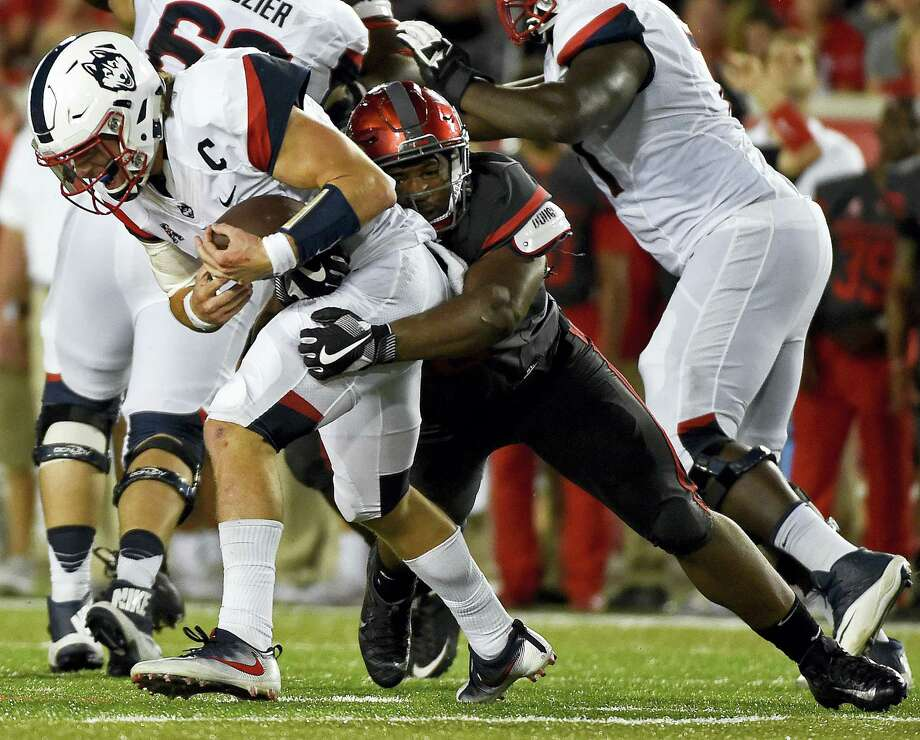 UConn quarterback Bryant Shirreffs, left, is sacked by Houston defensive tackle Ed Oliver in the second half against the Houston Cougars last Thursday. The Huskies host Cincinnati on Saturday. Photo: ERIC CHRISTIAN SMITH — THE ASSOCIATED PRESS  / FR171023 AP