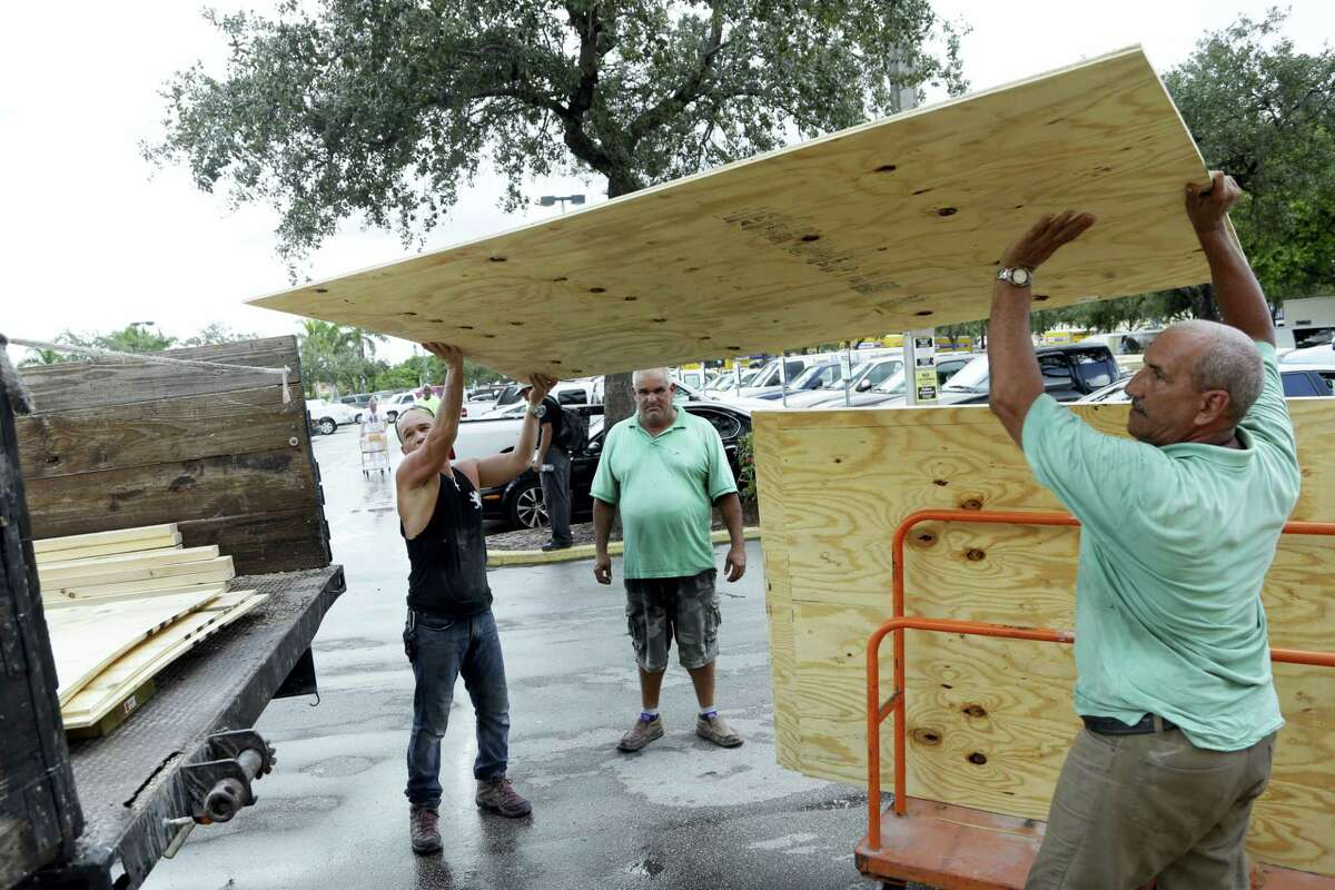 Jose Luis, left, and Miro Espana load plywood into a truck in preparation for Hurricane Matthew on Oct. 5, 2016 in Miami. People boarded up beach homes, schools closed, and officials ordered evacuations along the East Coast on Wednesday as Matthew tore through the Bahamas and took aim at Florida.