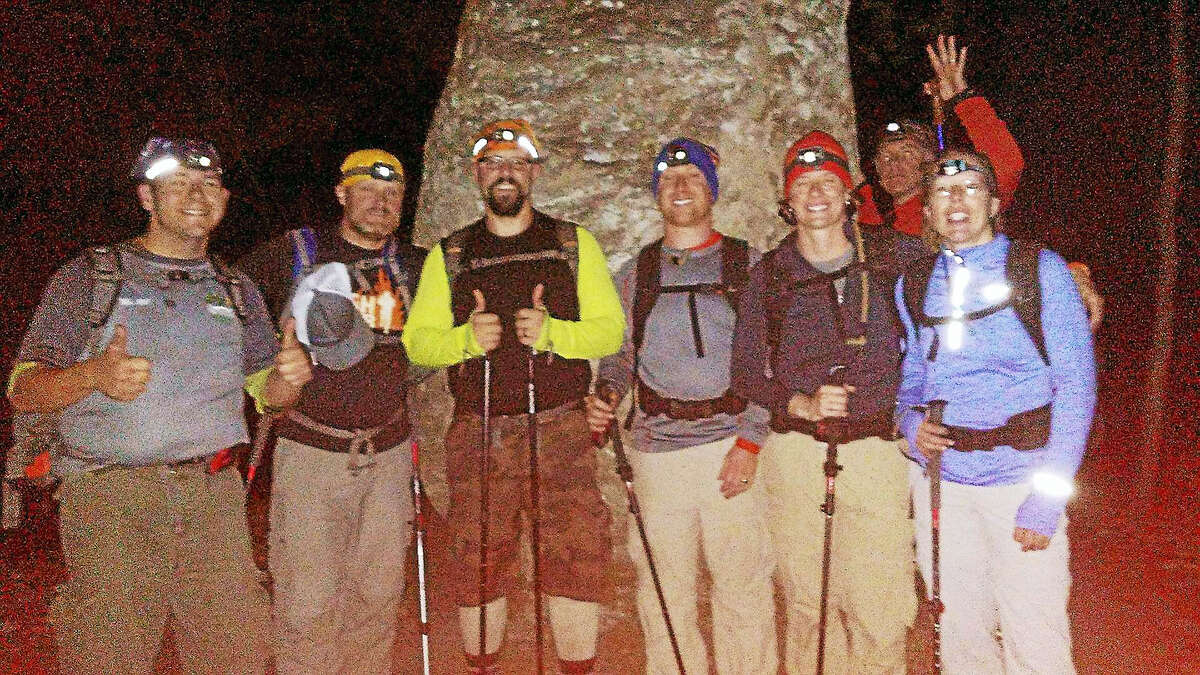 Hikers pose for a group shot at night.