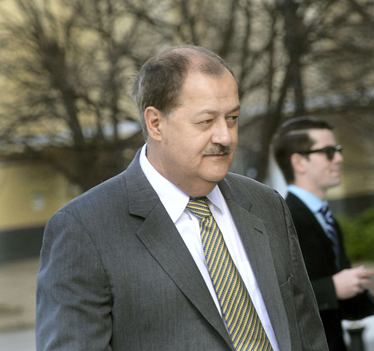 In an April 6, 2016 photo, former Massey CEO Don Blankenship is escorted by Homeland Security officers from the Robert C. Byrd U.S. Courthouse in Charleston, W.Va. Blankenship, who was sentenced to a year in jail and a $250,000 fine for his role in the Upper Big Branch Mine explosion, has declared himself an 'American political prisoner' on his blog, blaming others for the 2010 mine explosion that killed 29 men and led to the former West Virginia coal operator's imprisonment.