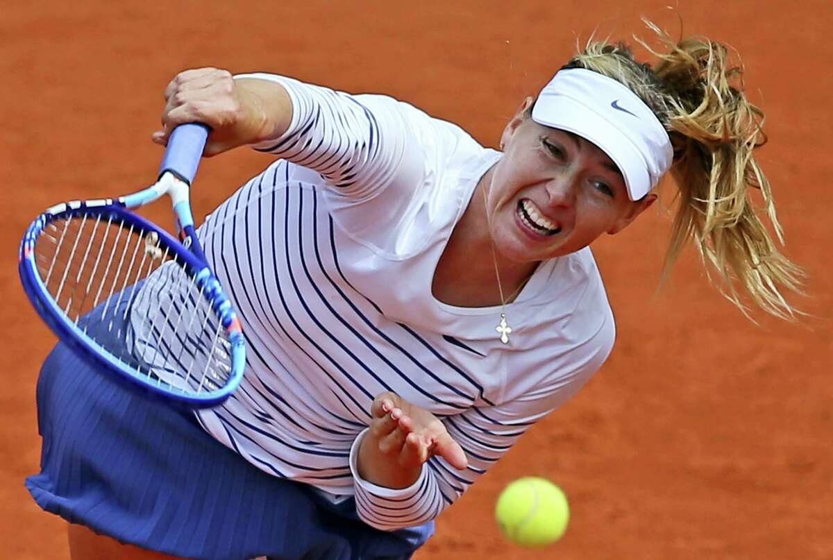 In this June 1, 2015 photo, Russia's Maria Sharapova serves the ball to Lucie Safarova of the Czech Republic during a fourth round match of the French Open tennis tournament at Roland Garros Stadium in Paris, France.