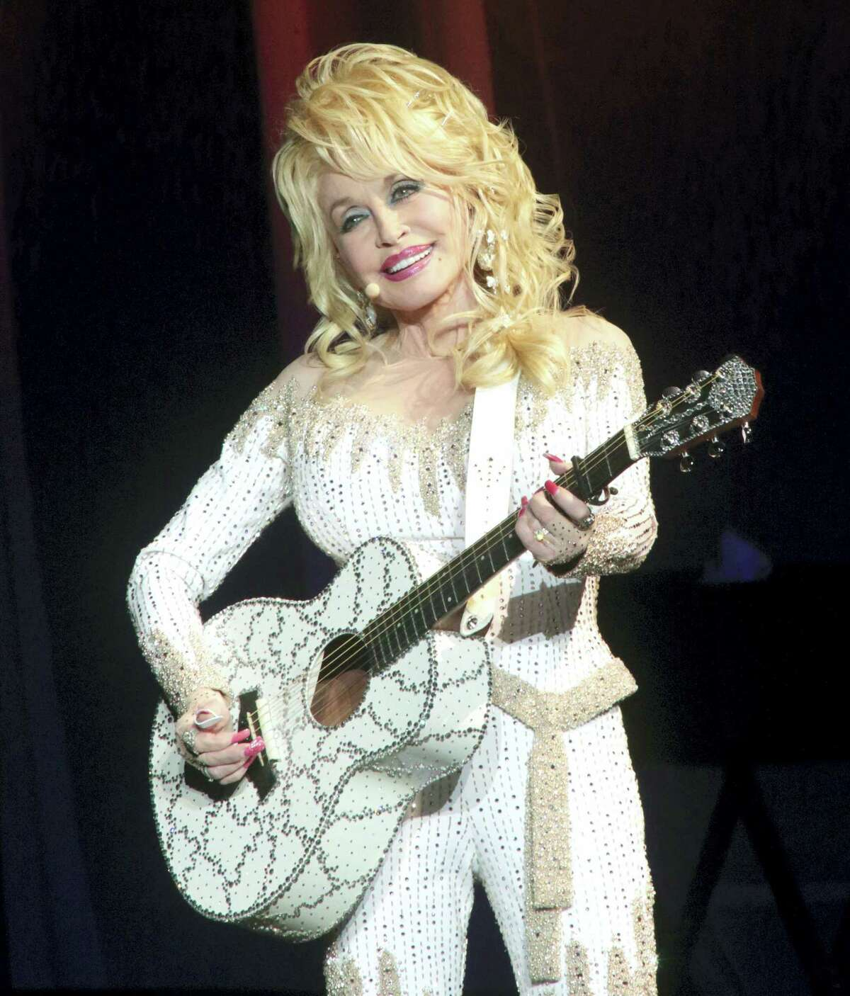 In this June 15, 2016, file photo, Dolly Parton performs in concert during her Pure & Simple Tour in Philadelphia. Parton will receive the Willie Nelson Lifetime Achievement Award at the 50th annual Country Music Association Awards in Nashville, Tenn., on Nov. 2.