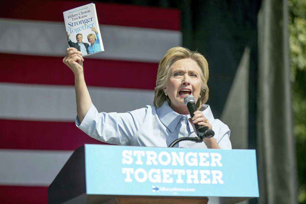 """Democratic presidential candidate Hillary Clinton holds up the book """"Stronger Together"""" as she speaks in Cleveland, Ohio, Sept. 5."""