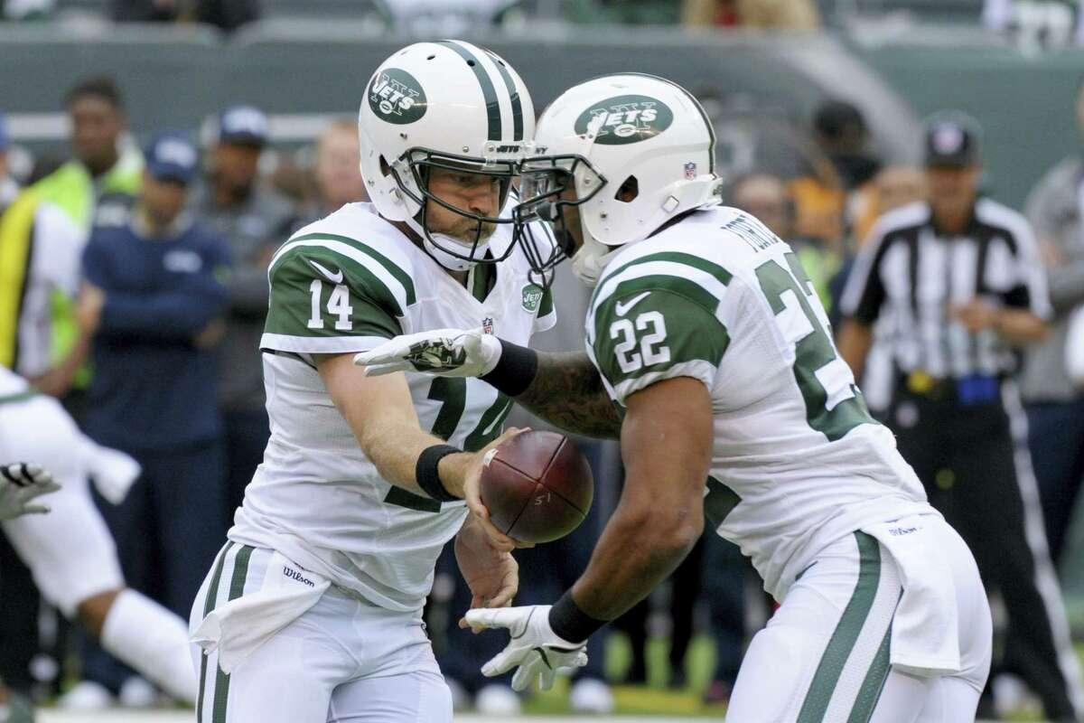 Jets quarterback Ryan Fitzpatrick, left, hands the ball off to running back Matt Forte on Sunday.
