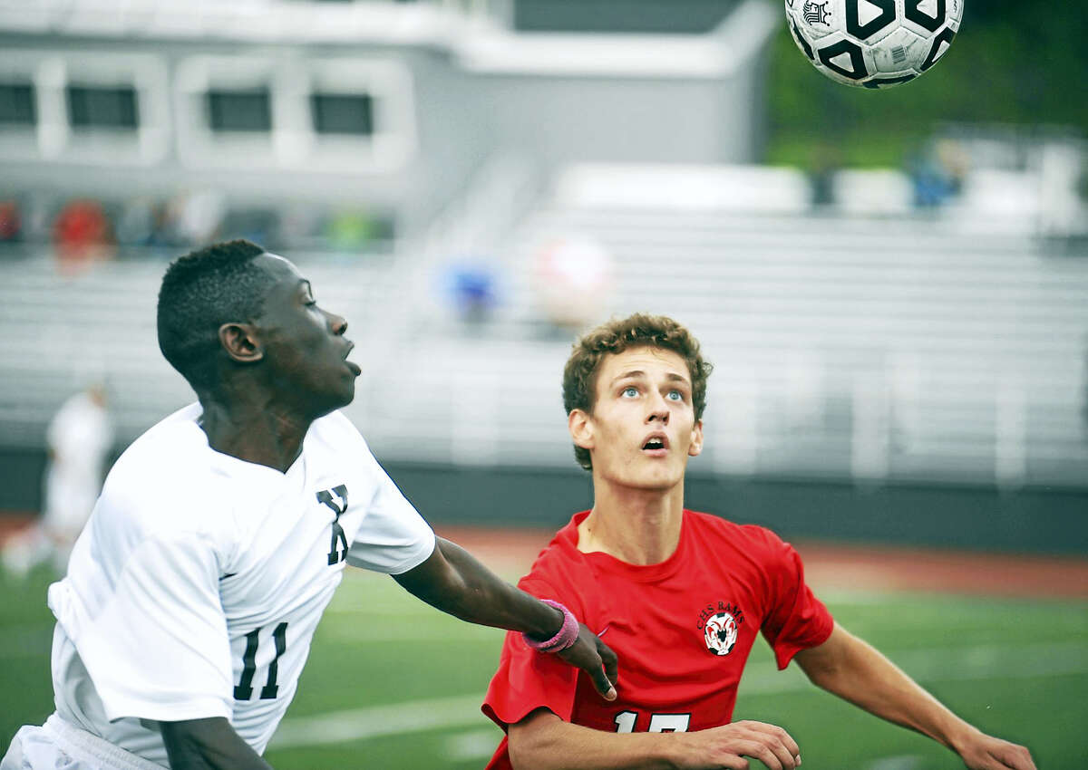 Xavier senior Brandon Dickens, left, and Cheshire senior Pascal Preudhomme battle for the 50/50 ball Monday at McHugh Field.