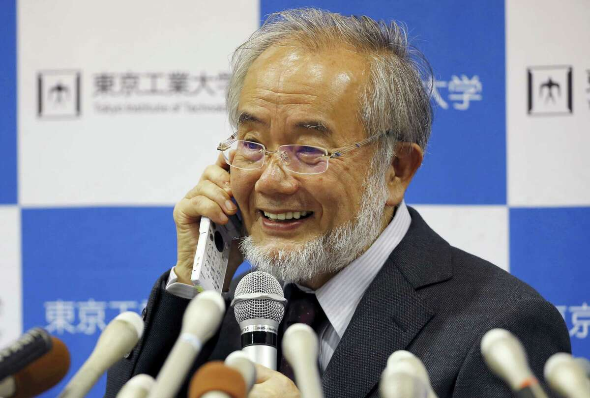 Nobel Prize winner Yoshinori Ohsumi smiles as he speaks with Japanese Prime Minister Shinzo Abe on a mobile phone during a press conference at the Tokyo Institute of Technology in Tokyo Monday, Oct. 3, 2016. Ohsumi won the Nobel Prize in medicine on Monday for discoveries on how cells break down and recycle content, a garbage disposal system that scientists hope to harness in the fight against cancer, Alzheimer's and other diseases. (AP Photo/Shizuo Kambayashi)