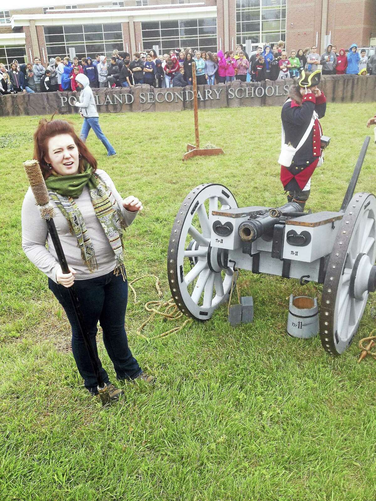 Teacher Kayla Pittman stands in front of the cannon as dozens of Portland middle-school students look on during Colonial Experience Day late last week.