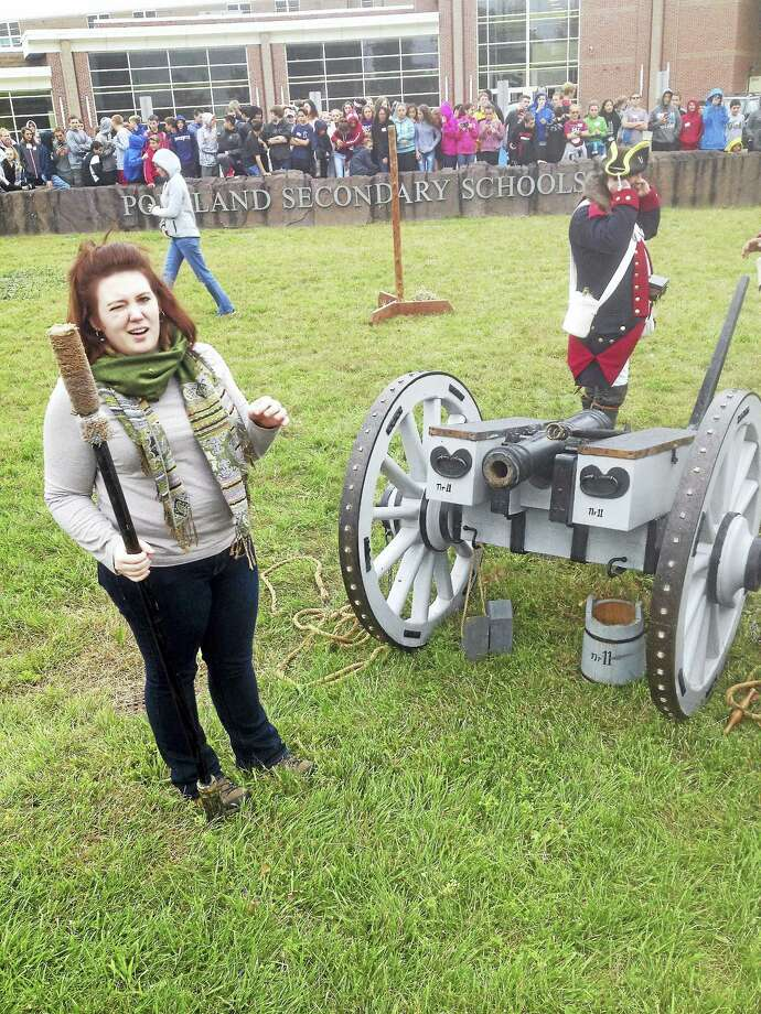 Teacher Kayla Pittman stands in front of the cannon as dozens of Portland middle-school students look on during Colonial Experience Day late last week. Photo: Jeff Mill — The Middletown Press