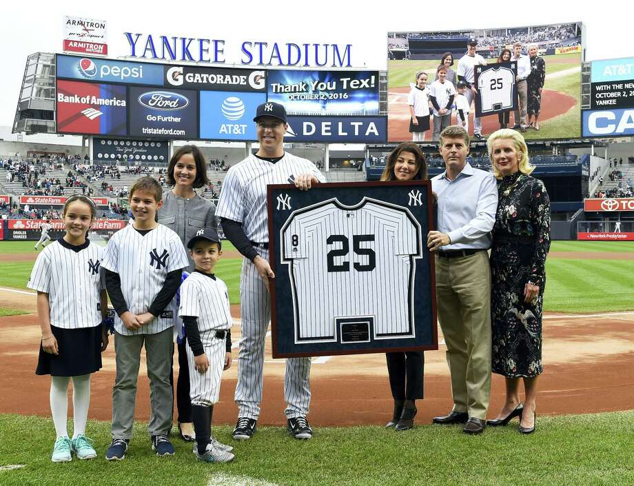 Yankees first baseman Mark Teixeira with his wife, Leigh, and children Jack, Addy and Will, stand with his framed jersey presented by Hal Steinbrenner and his wife, Christina DiTullio, left, and Jennifer Steinbrenner during a ceremony on Sunday. Photo: Kathy Kmonicek — The Associated Press  / FR170189 AP