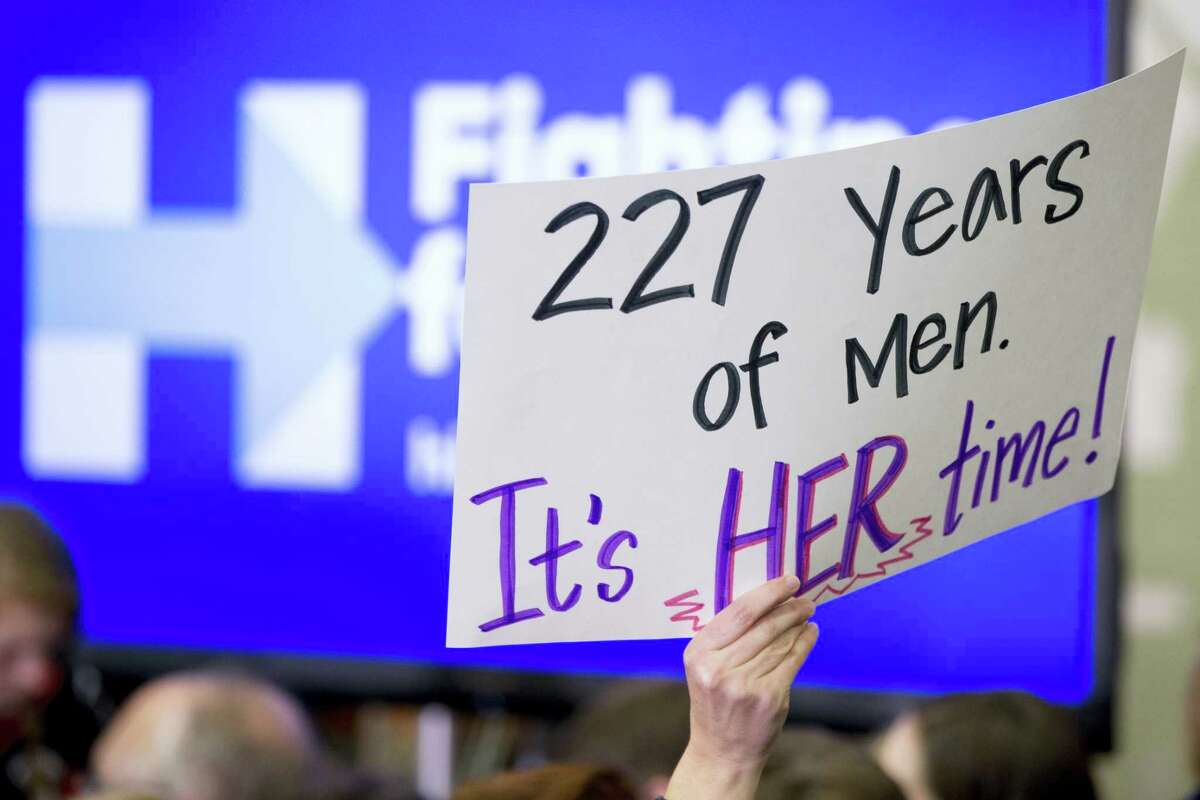 """FILE - In this Saturday, Jan. 30, 2016 file photo, a member of the audience holds a sign that reads, """"227 Years of Men. It's HER Time!"""" during a rally for Democratic presidential candidate Hillary Clinton at Washington High School in Cedar Rapids, Iowa. It's a complicated time for gender relations in the U.S., as the campaign pitting Clinton against Republican presidential nominee Donald Trump has underscored. (AP Photo/Andrew Harnik)"""