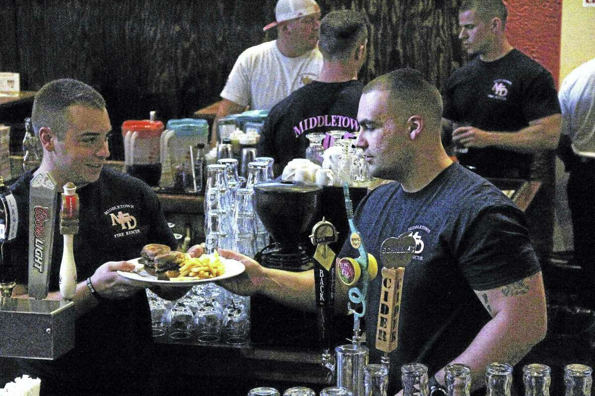 Friday's lunch crowd at Tuscany Grill in Middletown was a steady stream of diners — which kept Middletown firefighters who donated their time to serve dishes quite busy.