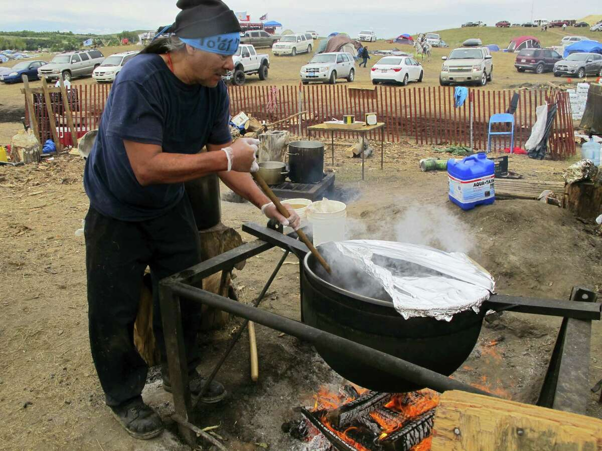 In this Sept. 9, 2016 photo, Phil Daw Sr., of Albuquerque, New Mexico, helps cook beef stew to feed hundreds at an encampment near North Dakota's Standing Rock Sioux reservation. The sprawling encampment that's a protest against the four-state Dakota Access oil pipeline has most everything it needs to be self-sustaining — except a federal permit to be there.