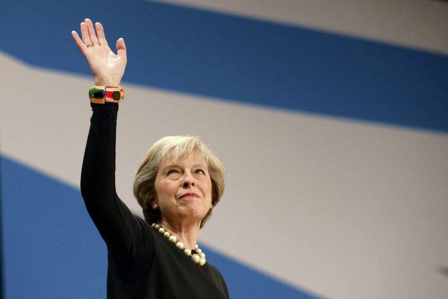 Britain's Prime Minister Theresa May waves to part members assembled to hear her speech at the Conservative Party Conference in Birmingham, England on Sunday Oct. 2, 2016. Britain will trigger the formal process for leaving the European Union before April 2017, May said Sunday, putting to rest weeks of speculation on the timing of the move. Photo: Ben Birchall/PA Via AP  / PA
