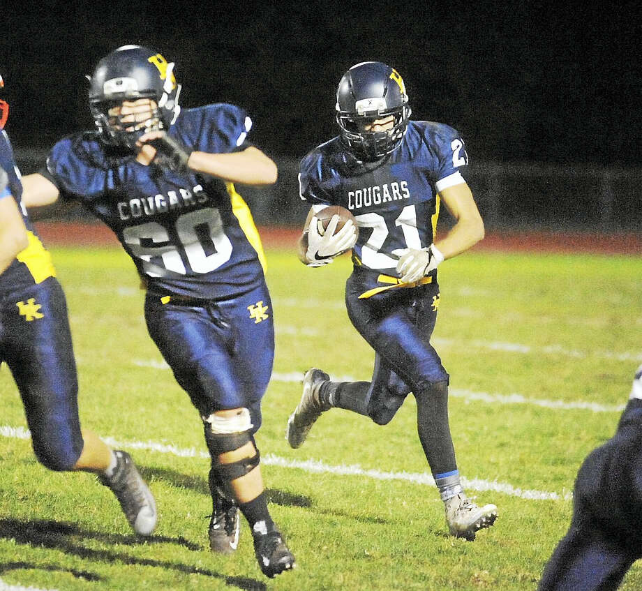 H-K senior Noah Vinci (21) runs behind the blocking of Kevin Dougherty (60). Vinci scored three touchdowns in the Cougars' 33-22 win over Coginchaug on Thursday night. Photo: Jimmy Zanor – The Middletown Press
