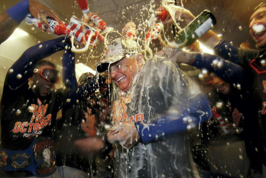 Mets manager Terry Colllins is doused with champagne and beer in the clubhouse after Saturday's win over the Phillies. Photo: Laurence Kesterson — The Associated Press  / FR170723 AP