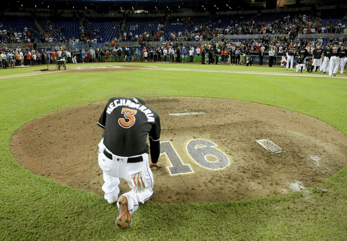 The Marlins' Adeiny Hechavarria (3) touches the pitcher's mound with the No. 16 on it in honor of Marlins pitcher Jose Fernandez, who was killed in a boating accident in Miami last Sunday.