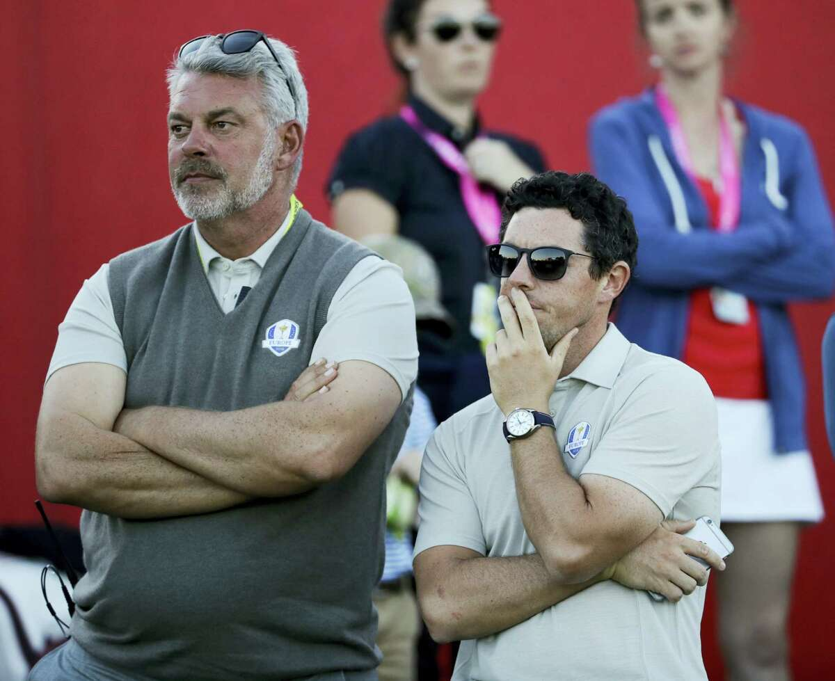 Europe captain Darren Clarke and Europe's Rory McIlroy watch on the 17th hole Saturday.