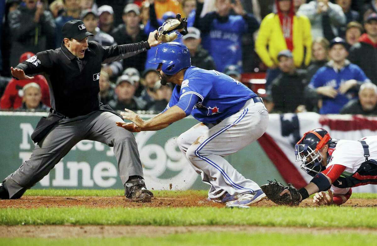 The Blue Jays' Dalton Pompey, center, scores in front of Red Sox catcher Christian Vazquez in the ninth inning on Saturday.