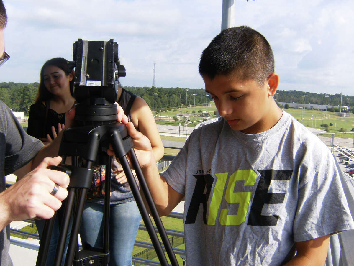New Caney ISD student Ethan Torres demonstrates how to set up a camera during the Dream Team's first day of training at the Texan Drive Stadium. The Dream Team works with broadcasting equipment, cameras, screens, sound systems and more at the stadium.