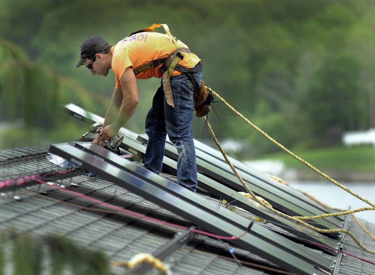 Avi Baron with Danbury-based Ross Solar Group helps install solar panels on a Brookfield home.